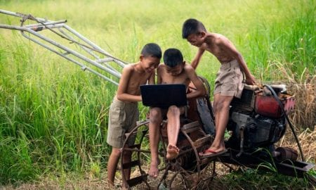 children on farm with laptop