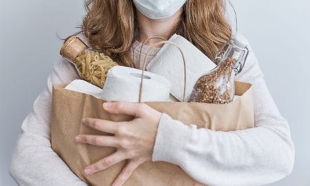 consumer with groceries and mask