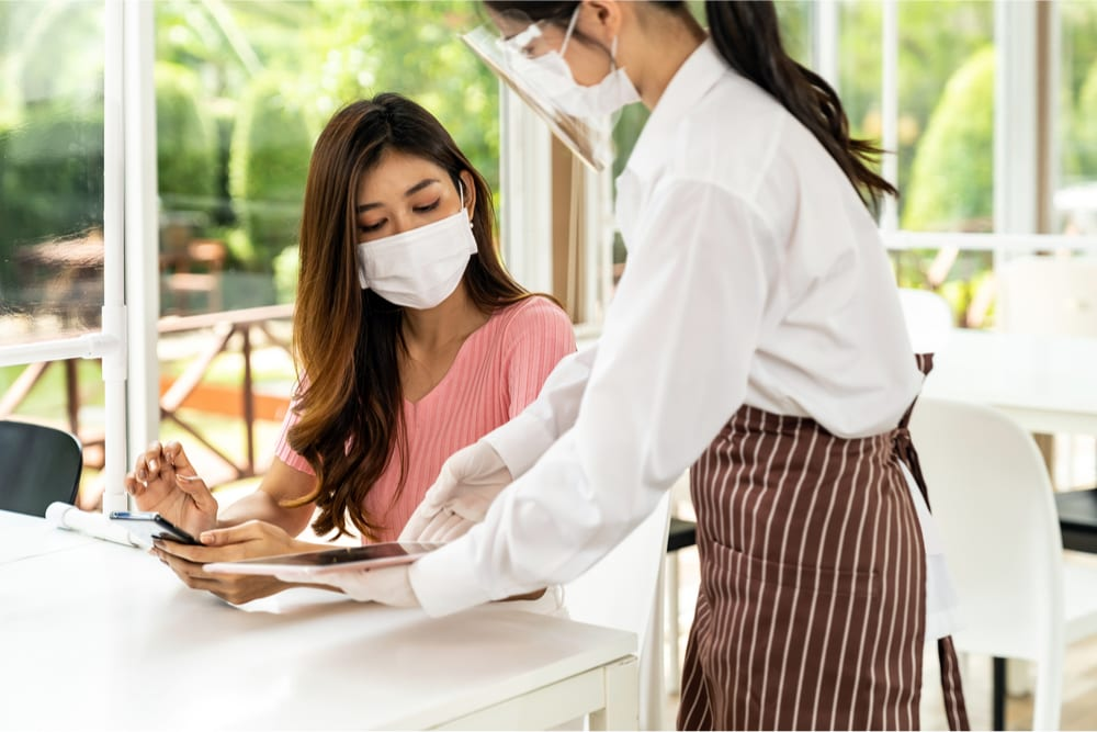 restaurant server and patron wearing face masks